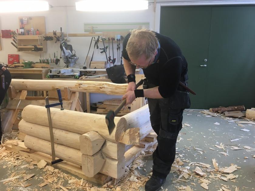 Jens kappar stokken i nova med øks. Foto: Roald Renmælmo