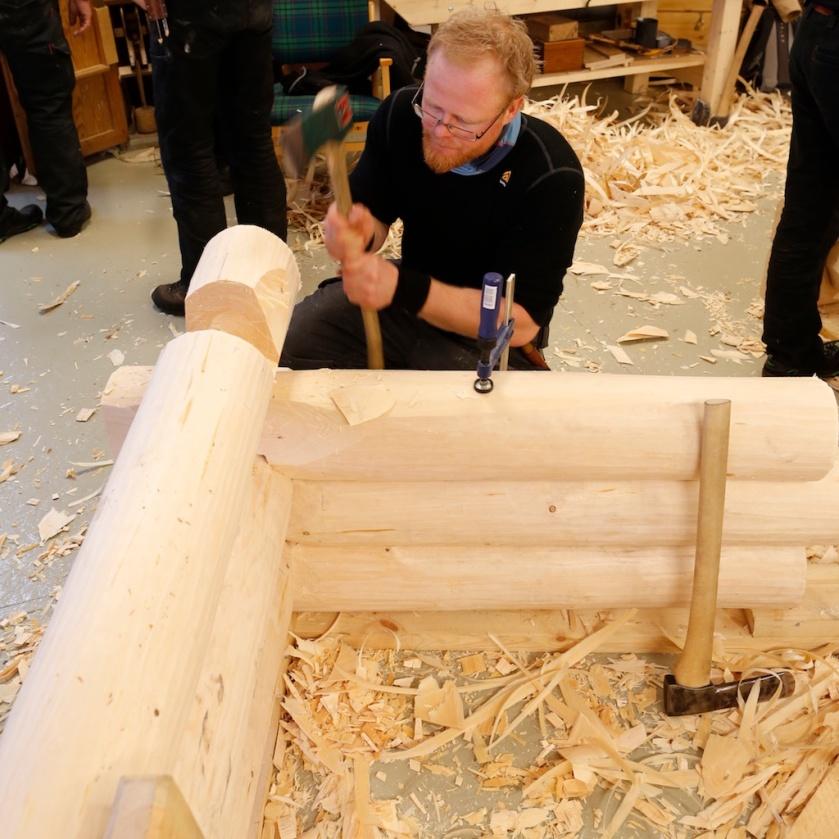 Jens hogger kinningar på ein stokk til prøvetømringa. Foto: Roald Renmælmo