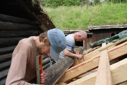 Ferdig hogd nåmtro, legges på taket, og sperrebreddene loddes opp på nåmtroa, og sperrehakket hogges ut med øks. Foto. Henning Jensen