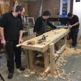 Pål, Peter og Georgios arbeider på den nye høvelbenken til Trond.