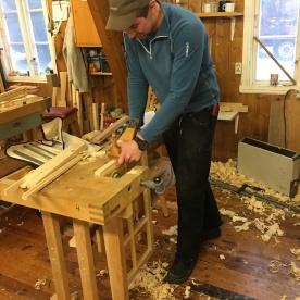 Sven i arbeid med å høvle material.
