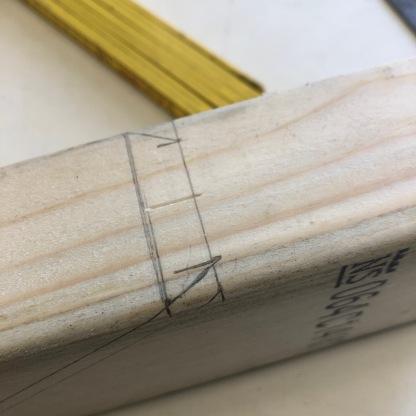 Avfasingen på stikksperren måles på grunnrisset fra senterlinjen mot omrisset til anleggssperrer og avsettes på emnet sammen med vinkelen til anleggsflaten mot søylen